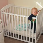 Baby In White Mini Crib Near White Cabinet