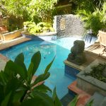 Backyard Landscaping Of Swimming Pool With Decorative Statue And Plants