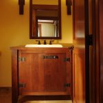 Bathroom vanity with sink and faucet in mission style a vanity mirror with wooden frame a pair of vanity light fixture