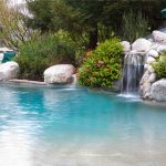 Beautiful Waterfall COmes From Rocks On Pool With Blue Water