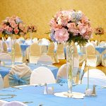 Beautiful-and-sweet-wedding-reception-with-tall-centerpieces-of- pink-roses-and-blue hydrangeas-in-the-tall-glass containers-and-white-orchids-and-tables-and-chairs