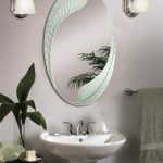 Beautiful oval mirror with leaves shaped frame a small sink and faucet a pair of vanity light fixtures