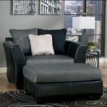Black leather oversized recliner furniture with white pillow and an table ottoman