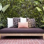 Black outdoor daybed mattress with floral pillowcases and pink and white pillowcases