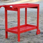 Bright red painted wood bar cart idea with a pair of front wheels