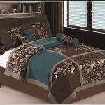 Brown and teal bedding with floral pattern  floral pattern pillows in brown and teal colors round black coated wooden side table with white decorative vase and flowers a king bed frame with headboard