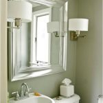 Brushed nickel mirror for bathroom a pair of vanity lighting fixtures a toilet a free standing sink with faucet