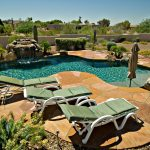 Cool Landscaping Swimming Pool View WIth Pool Chairs And Waterfall