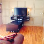 Cool And Modern Black Wood TV Console With Black Shelving Units With Wheels At The Bottom A Large Flat TV Set A Pair Of Classic Table Lamps A Media Player