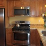 Cream kitchen countertop with double sinks and faucet a large gas stove base and wall wood kitchen cabinet system
