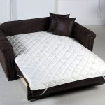 Dark brown leather loveseat sleeper with white comforter and a pair of leather cased pillows