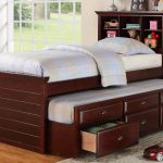 Dark brown trundle with bookcase in headboard a pull out bed and drawer system