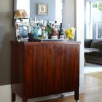 Darker coated wooden bar cabinetry with wheels