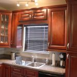 Darker Coated  Wooden Kitchen Cabinet Clearance Idea With Lower Metal Handle L Shape Natural Stone Counter With Steel Sinks And Steel Faucet A Small Kitchen Window With Blinds A Pendant Lamp