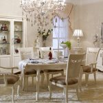Dining room decor in white French theme with white dining chairs white dining table white armoir storage a white dishware cabinet system brushed nickel painting crystal pendant chandelier