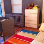 Double Grey Baby Crib In Small Room With White Cabinet And Colorful Rug Next To Bed