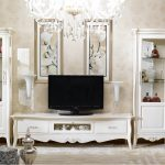 Entertainment room in French inspired theme with a pair of French style tall cabinet storage units a French style media console a unit of crystal pendant chandelier