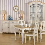 French style dining room decor idea with wood top dining table and wood seat dining chairs a vintage dining cabinet with a pair of table lamps an armoire with white trims and glass door