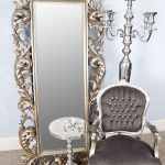 Full looking mirror with antique metal frame a classic chair round metal side table in classic style