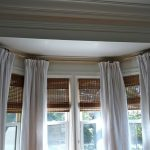 Gold toned metal rod mounted on ceiling for bay window curtains white window curtains  glass windows with rolled wood blinds