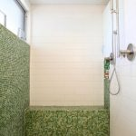 Green And White Bathroom Shower Area With High Ceiling