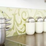 Green floral themed wallpaper for modern kitchen backsplash some small containers for pepper powder salt and sugar