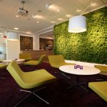 Green plants room divider several modern green chairs white round tables dark maroon area rug