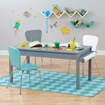 Grey craft workstation for kids three chairs for kids in white grey and blue colors a medium size rug in light and deep blue color schemes V shaped wall bookcases