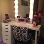 Hollywood-vanity-table-with-white-lighted-mirror-and-black-chair-and-white-dresser-with-cosmetics-also-brown-curtain-and-white-color-wall