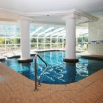 Indoor Swimming Pool Design WIth Tile Deck And Sun Room