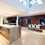 Large Modern Kitchen With Brown Brick Wall And Wooden Floor