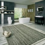 Large Bathroom Rug In Neutral Color A Narrow White Bathtub A Modern White Toilet Modern Wall Shelving Units  Black Minimalist Bathroom Vanity With White Sink And Faucet A Frameless Oval Mirror