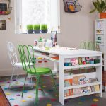 Large white craft desk design with under shelf and bookcase at side of desk two green metal chairs and a white metal chair cute grey rug with colorful textured polka dot motifs
