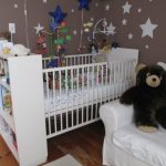 Larger baby crib with bookcase a white sofa for nurturing room