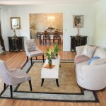 Light Living Rom With White Sofa And Table Two Grey Chairs Square Rug Hardwood Table Artistic Frame And Twins Cabinet At Room Corner