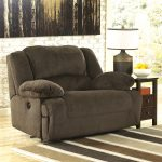 Light black oversized recliner sofa with armrests a wooden side table with drawers a table lamp a decorative bowl for fruits