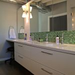 Long And Big Bathroom Cabinet With Green Tile Design And Wide Mirror Near Small Lamp