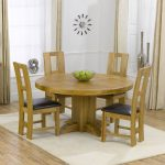 Low profile wood round table with four dining chairs with black leather cushion