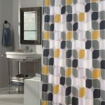 Mid century modern shower curtain with three tone colors for the pattern a small bathroom vanity with  sink and faucet a  framed mirror grey wool bathroom mat