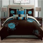 Modern bed furniture with grey headboard and beautiful floral pattern bedding and pillows in teal and brown colors a pair of darker brown coated wooden bedside tables with a pair of table lamps