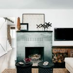 Modern fireplace with metal mantel some windmill miniatures as the decoration a wall mounted TV set over log storage round backless seater round table an indoor daybed with white bedding