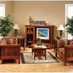 Modern living room with mission style living room wood chairs with cushions a media cabinet twin side tables with twin table lamps a classic area rug two corner decorative plants