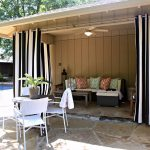 Outdoor patio drape idea in white and black strip pattern a set of patio furniture in white a small sectional with pillows for outdoor a ceiling fan with lamp for patio
