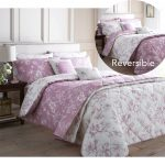 Pink Purple And White Color Bedding Design On Bed Cover And Pillows White Wall Lamp Hardwood Floor