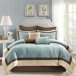 Queen bed furniture with white headboard and teal brown bedding and pillows white round bedside table small white vase for decorative plant