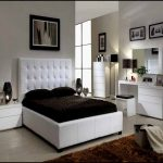 Quuen sized bed furniture with higher white leather headboard dark brown bedding and dark brown pillows a pair of white minimalist bedside tables a white bedroom vanity with white framed mirror
