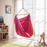Red Fabric Hanging Swing In White Room With Green Rug And Wooden Storage Place