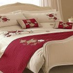 Red and white comforter with rose pattern a luxurious classic bed furniture with headboard and footboard a classic white side table