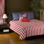 Red and white lines comforter with American flag motif pillows modern wood bedside table with single under shelf a small table lamp with white cap