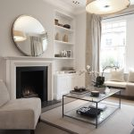 Round mirror with brushed nickel frame over a simple modern white fireplace mantel built in shelving unit a white armless chair a glass top coffee table with black metal frame